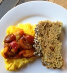 Simple weekend breakfast of scrambled eggs topped with quick-sautéed cherry tomatoes with a slice of homemade whole-grain seeded soda bread